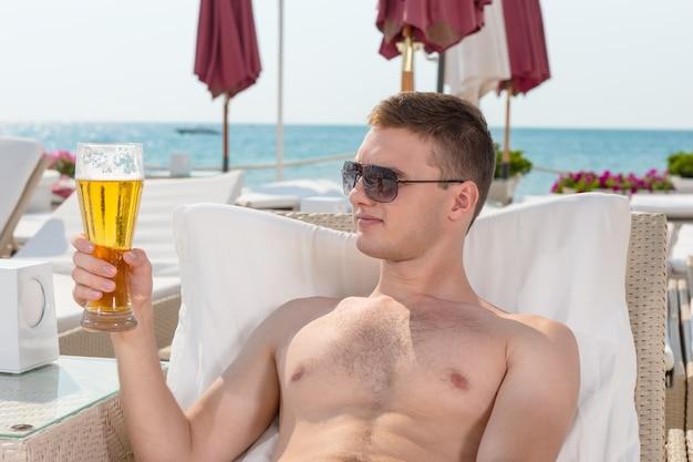 Glimlachende knappe jongeman met een zonnebril die op een ligstoel aan de kust ligt en geniet van een biertje op zijn zomervakantie