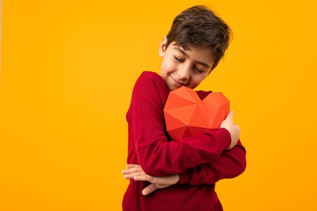 Glimlachende knappe jongen met papieren hart voor valentijnsdag op oranje achtergrond.