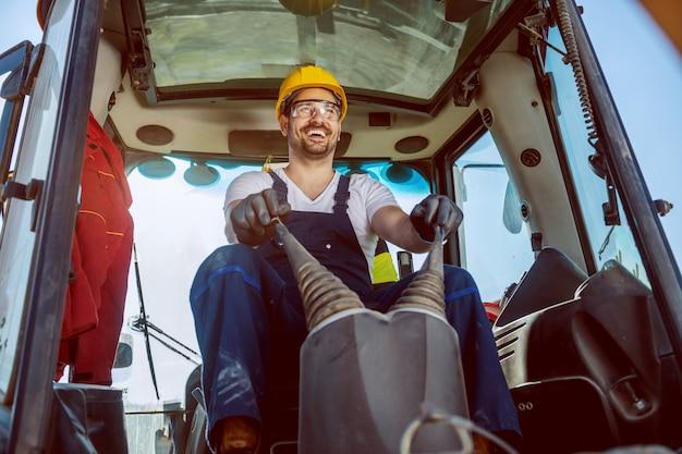 Glimlachende knappe kaukasische arbeider in het algemeen en met helm op hoofd drijfgraafwerktuig.