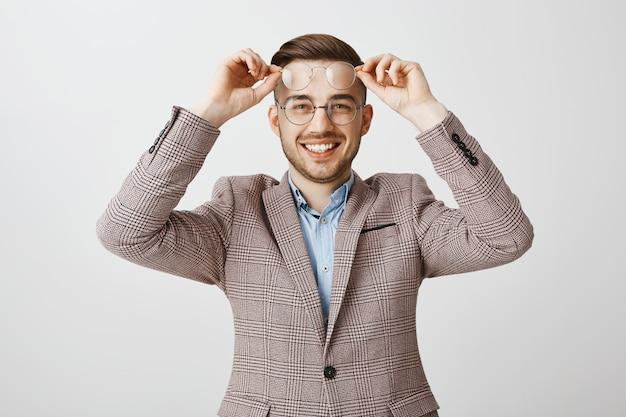 Glimlachende knappe kerel in kostuum probeert nieuwe glazen, brillen te plukken