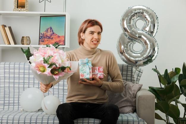 Glimlachende knappe kerel met zijn ogen op een gelukkige vrouwendag die een cadeautje vasthoudt met een boeket op de bank in de woonkamer