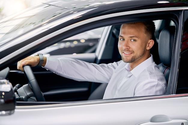 Glimlachende knappe man autorijden