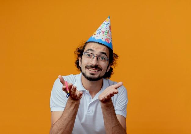 Glimlachende knappe man die een bril en een verjaardagspet draagt die handen uitstrekt die op oranje muur worden geïsoleerd