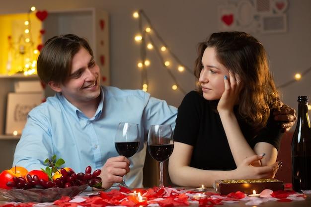 Glimlachende knappe man die een glas wijn vasthoudt en op valentijnsdag naar een tevreden mooie vrouw kijkt die aan tafel in de woonkamer zit