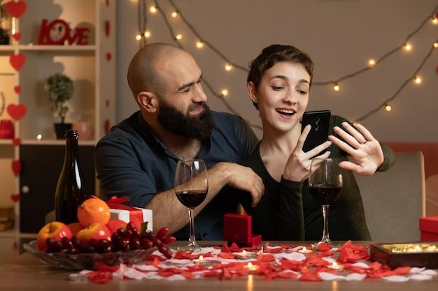 Glimlachende knappe man die op valentijnsdag naar een tevreden mooie vrouw kijkt die een foto neemt van haar ring aan de vinger zittend aan tafel in de woonkamer