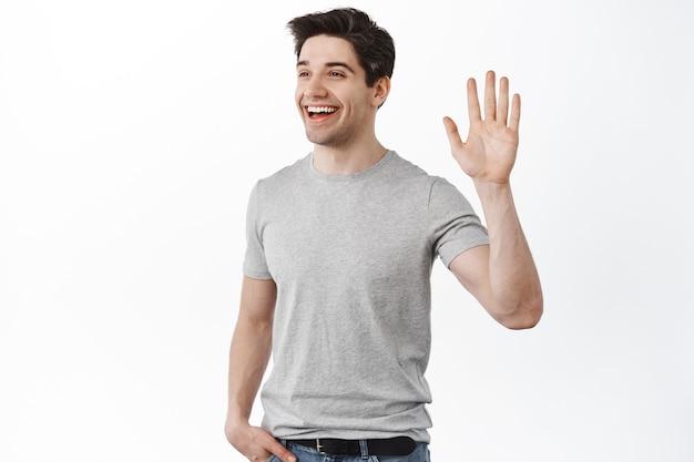 Glimlachende knappe man die opzij kijkt en zwaait, hallo zegt tegen een vriend, nonchalant in een ontspannen pose tegen een witte muur staat
