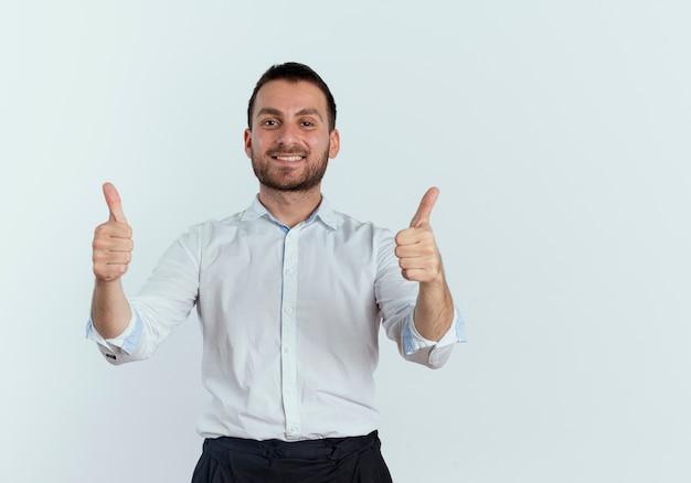 Glimlachende knappe man duimen omhoog met twee handen geïsoleerd op een witte muur