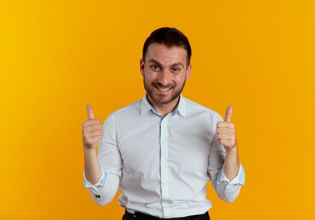 Glimlachende knappe man duimen omhoog met twee handen geïsoleerd op oranje muur