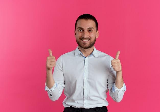 Glimlachende knappe man duimen omhoog met twee handen geïsoleerd op roze muur