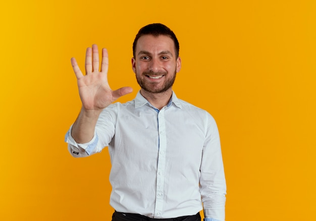 Glimlachende knappe man gebaren vijf met hand geïsoleerd op oranje muur