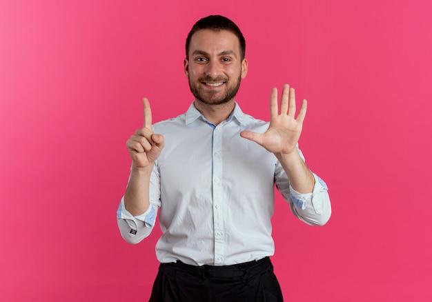 Glimlachende knappe man gebaren zes met handen geïsoleerd op roze muur
