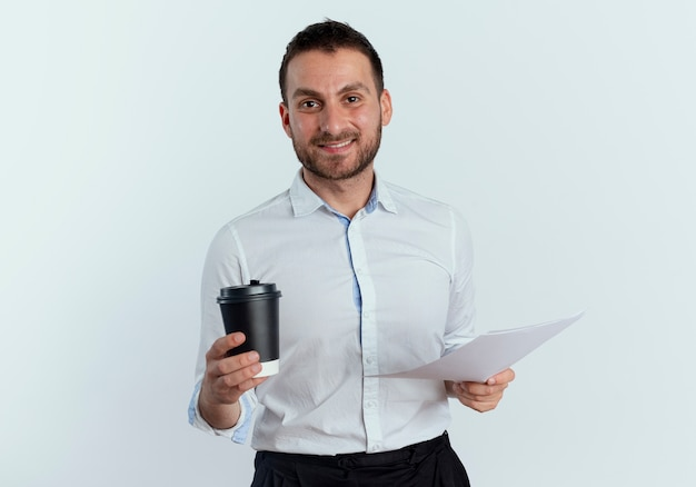 Glimlachende knappe man houdt koffiekopje en vellen papier geïsoleerd op een witte muur