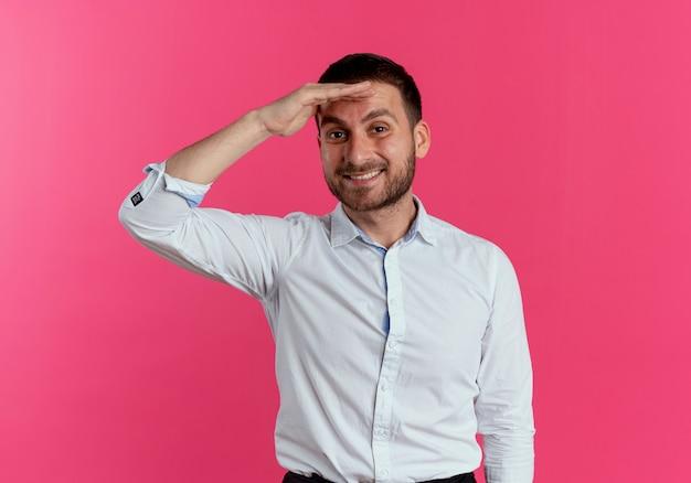 Glimlachende knappe man houdt palm op voorhoofd geïsoleerd op roze muur