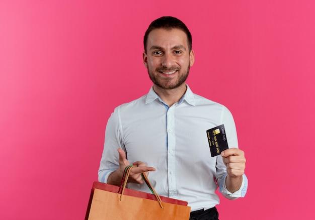 Glimlachende knappe man houdt papieren boodschappentassen en creditcard geïsoleerd op roze muur