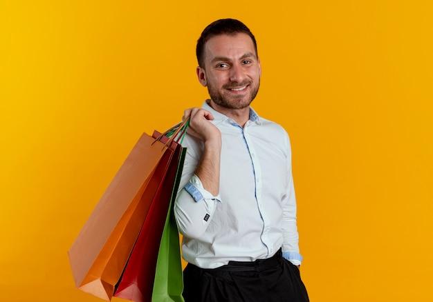 Glimlachende knappe man houdt papieren boodschappentassen op schouder op zoek geïsoleerd op oranje muur