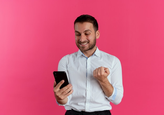 Glimlachende knappe man houdt vuist vasthouden en kijken naar telefoon geïsoleerd op roze muur