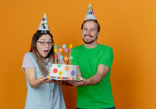 Glimlachende knappe man in feestmuts houdt verjaardagstaart en verrast jong meisje met feestmuts houdt en kijkt naar geïsoleerde cake