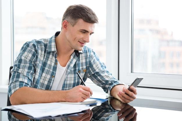 Glimlachende knappe man in geruit hemd die schrijft en mobiele telefoon gebruikt