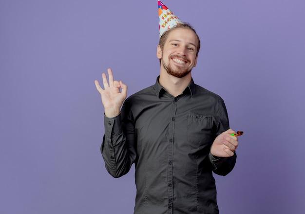 Glimlachende knappe man in verjaardag glb houdt fluitje en gebaren ok handteken geïsoleerd op paarse muur