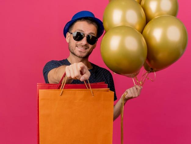 Glimlachende knappe man in zonnebril met blauwe feestmuts houdt helium ballonnen en papieren boodschappentassen wijzend naar voorzijde geïsoleerd op roze muur met kopie ruimte