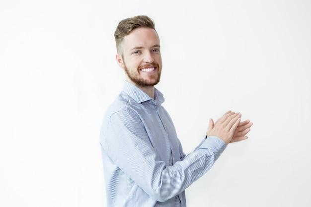 Glimlachende knappe man klappende handen