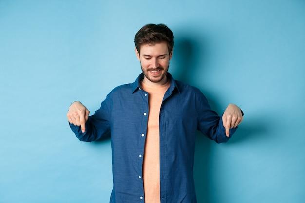 Glimlachende knappe man met baard, kijkend en wijzend naar beneden op banner, speciale aanbieding uitchecken, staande op blauwe achtergrond.