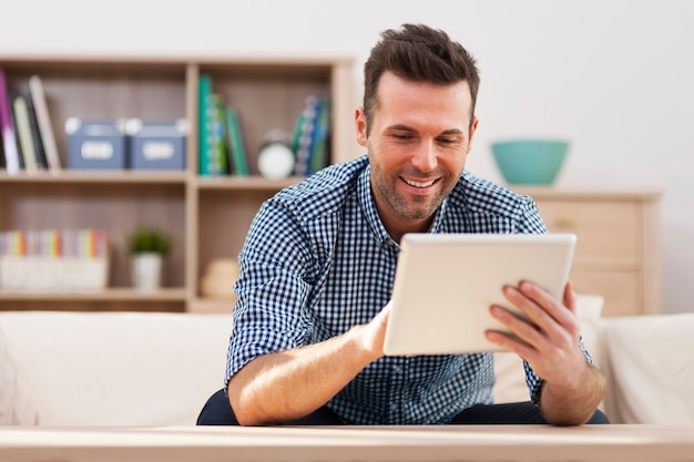Glimlachende knappe man met behulp van digitale tablet thuis
