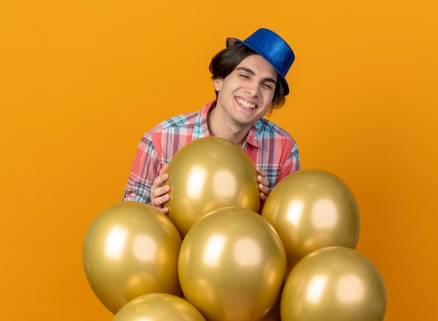Glimlachende knappe man met blauwe feestmuts staat met helium ballonnen geïsoleerd op oranje muur