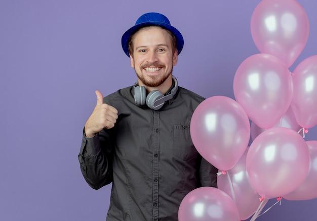 Glimlachende knappe man met blauwe hoed en koptelefoon op nek staat met helium ballonnen thumbs up geïsoleerd op paarse muur