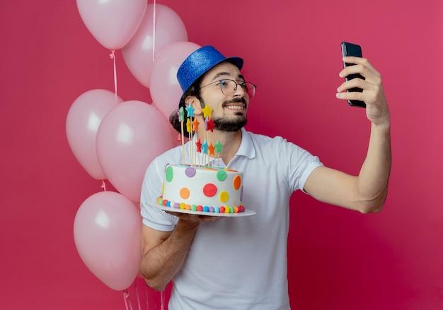 Glimlachende knappe man met bril en blauwe hoed die zich voor ballonnen bevindt die cake houden en een selfie nemen die op roze wordt geïsoleerd