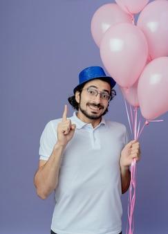 Glimlachende knappe man met bril en blauwe hoed met ballonnen en punten omhoog geïsoleerd op paars