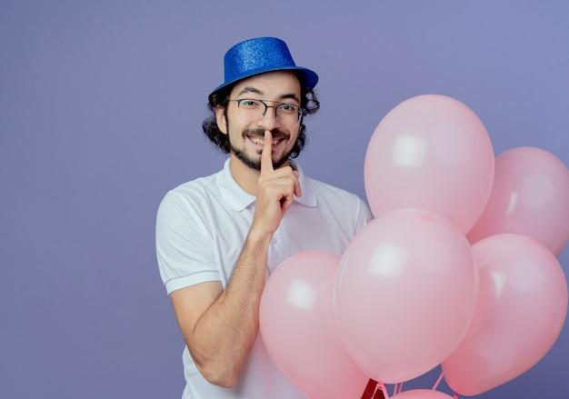 Glimlachende knappe man met bril en blauwe hoed met ballonnen en stilte gebaar geïsoleerd op paars tonen