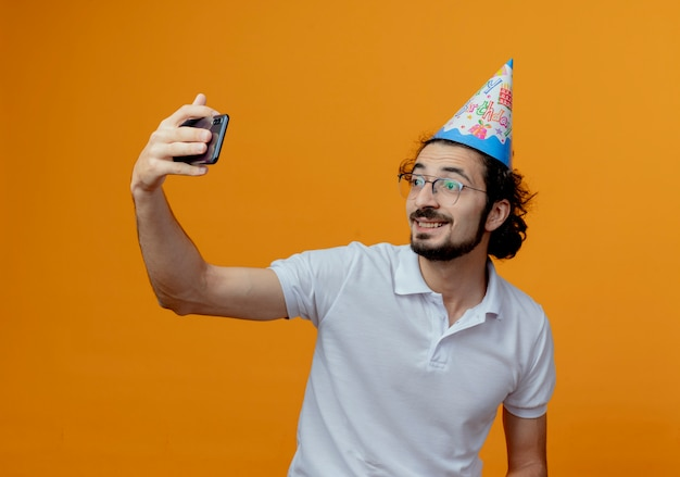 Glimlachende knappe man met bril en verjaardag glb neemt een selfie geïsoleerd op een oranje achtergrond