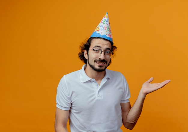 Glimlachende knappe man met bril en verjaardag glb-punten met hand aan kant geïsoleerd op een oranje achtergrond met kopie ruimte