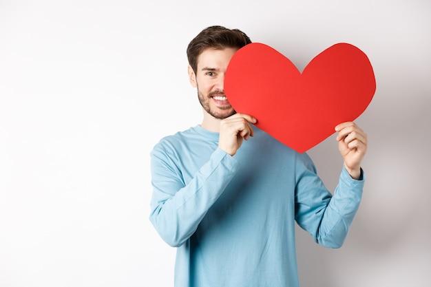 Glimlachende knappe man met romantisch rood hart meer dan de helft van het gezicht, vriendin verrassen op valentijnsdag, liefde bekentenis, staande op witte achtergrond.