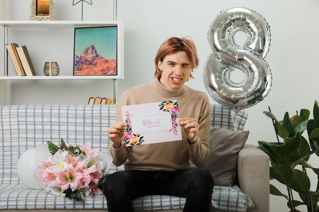 Glimlachende knappe man op gelukkige vrouwendag met wenskaart zittend op de bank in de woonkamer