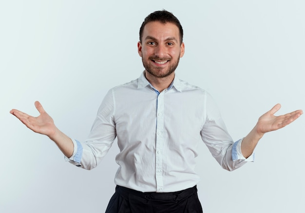 Glimlachende knappe man staat met open handen geïsoleerd op een witte muur