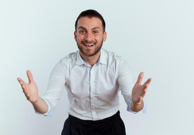 Glimlachende knappe man staat met opgeheven handen en kijkt geïsoleerd op een witte muur