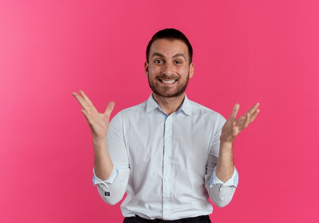 Glimlachende knappe man werpt handen geïsoleerd op roze muur