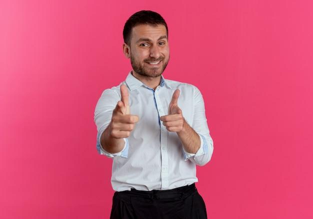 Glimlachende knappe man wijst met twee handen geïsoleerd op roze muur