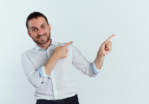 Glimlachende knappe man wijst naar kant met twee handen geïsoleerd op een witte muur