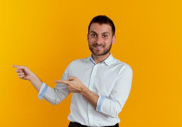 Glimlachende knappe man wijst naar kant met twee handen geïsoleerd op oranje muur