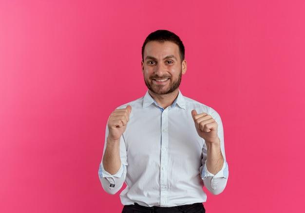 Glimlachende knappe man wijst naar zichzelf met twee handen geïsoleerd op roze muur