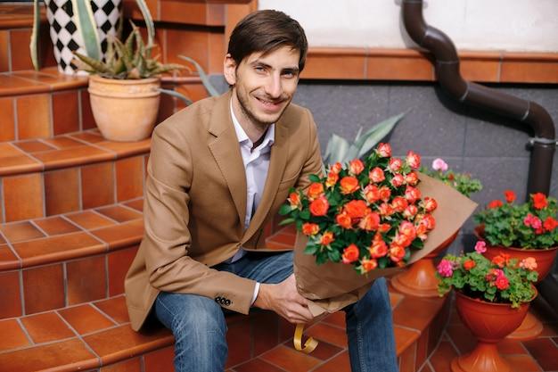 Glimlachende knappe mens die een bos van rozen houdt