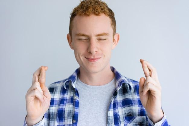 Glimlachende knappe mens die gekruist vingersgebaar toont