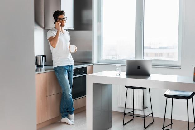 Glimlachende knappe mens die op smartphone in de ochtend thuis spreken