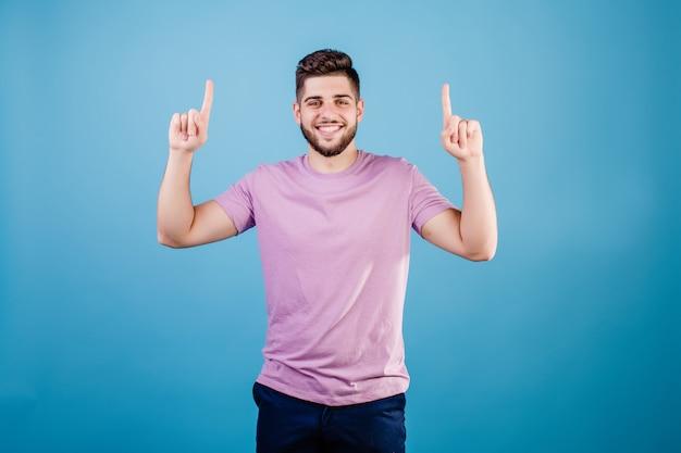 Glimlachende knappe mens die vinger richten op exemplaarruimte die op blauw wordt geïsoleerd