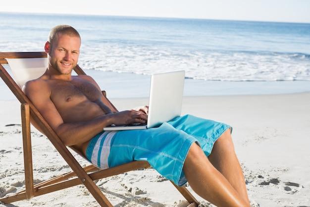 Glimlachende knappe mens die zijn laptop met behulp van terwijl het ontspannen op zijn ligstoel