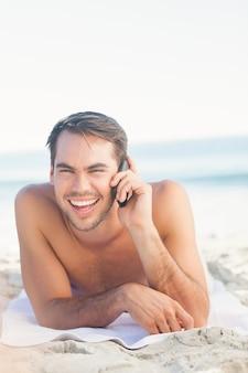 Glimlachende knappe mens op het strand die een telefoongesprek hebben