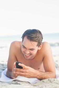 Glimlachende knappe mens op het strand die zijn cellphone gebruiken